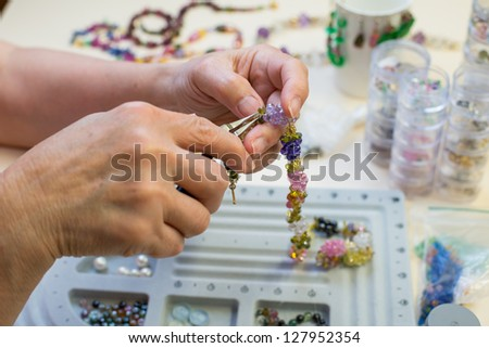 Pair of hands and pliers assembling a bead necklace. - stock photo