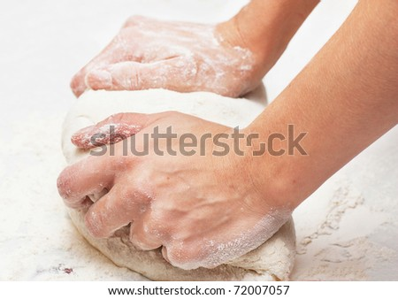 Pair of hands kneading pizza dough.