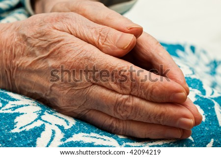 pair of hands of old woman in prayer on knees