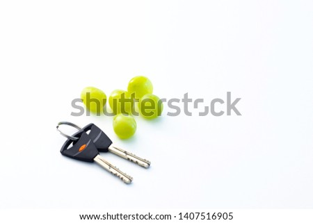 Pair of house keys and group of green grape fruits in the white table