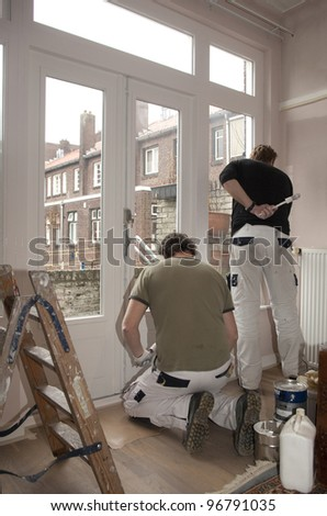 Pair of housepainters at work in a room