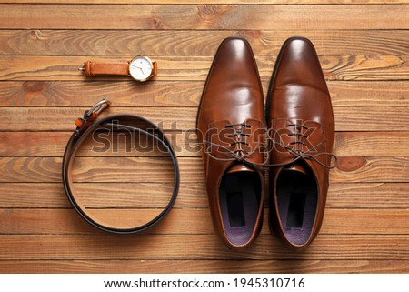 Pair of leather male shoes, watch and belt on wooden background Foto stock ©