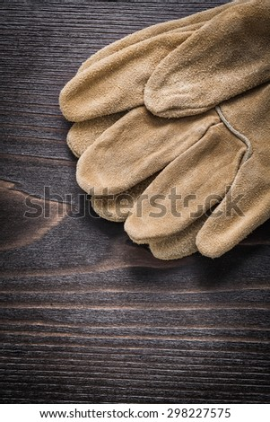 Pair of leather working gloves on vintage wooden board close up view construction concept.