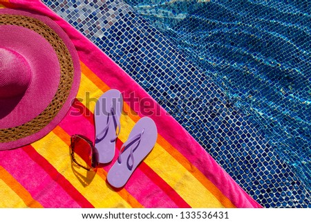Pair of light purple flip flops by the pool on a bright orange, pink, red and yellow striped towel with sunglasses and big pink floppy hat