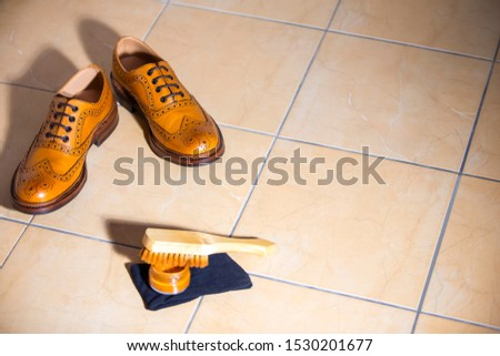 Pair of Luxury Male Full Brogued Tan Oxford Shoes. Placed Together with Shoe wax and Brush on Tiles Floor. Horizontal Shot #1530201677