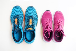 Pair of men's blue sneakers and pair of women's pink sneakers on white background. Concept love run. Run together. Family run. Top view.