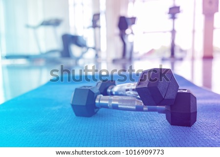 Pair of Metal dumbbells with blue yoga mat on wood floor, flare light in the gym with high contrast with copy space , sport equipment in gym concept