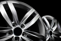 Pair of modern aluminium wheel rims isolated on black background.