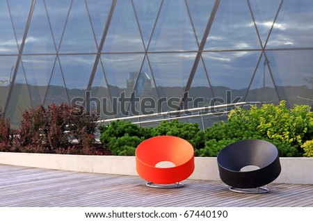 Pair of modern plastic benches at public space - stock photo
