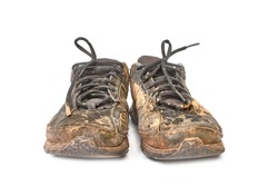 Pair of muddy shoes covered with mud