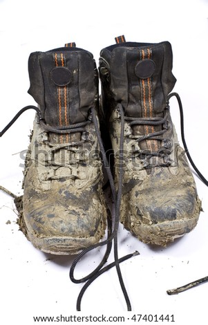 Pair of muddy , worn walking or hiking boots on a plain background