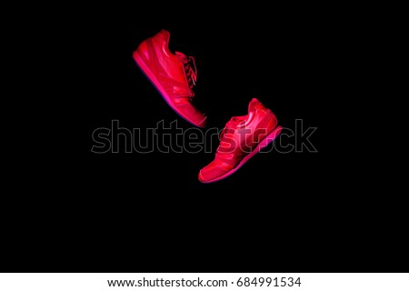 Pair of New Red Sneakers Isolated on Black Background. Copy Space for Your Text. Fashionable Leather Sports Shoes with laces. Horizontal Photo Banner for website  header Design. Sneaker in the air