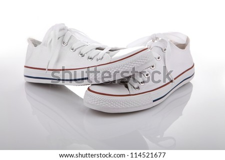 Pair of new white sneakers on white background with reflection
