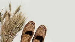 Pair of old bast shoes and a sheaf of wheat on a light background. Copy space.