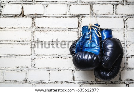 Pair of old blue and black boxing gloves hanging on white brick wall. Zdjęcia stock ©
