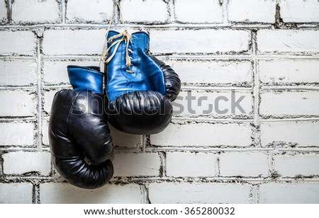 Pair of old blue boxing gloves hanging on white brick wall background. Zdjęcia stock ©