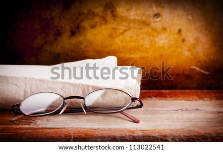 Pair of old eyeglasses on a wooden desk with a grunge background