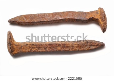 Pair of old rusty railroad spikes on a white background with shadows