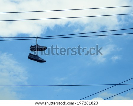 Pair of old sneakers hanging by their laces on a telephone wire
