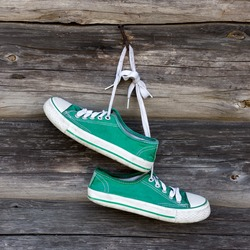 Pair of old sneakers hanging on the wall
