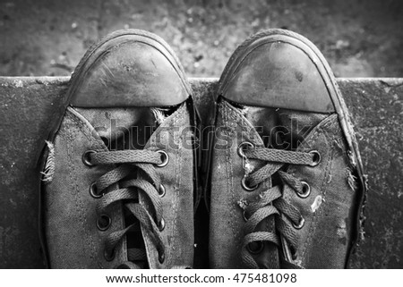 Pair of old sneakers standing on concrete stairs, closeup top view. Black and white retro stylized photo