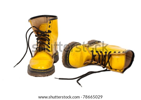 Pair of old yellow shoes on white background