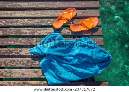 pair of orange flip-flops and a blue towel on the wooden planks of a jetty over the sea