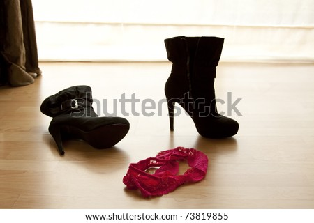pair of pink panties on a wooden floor next to a high heel boot