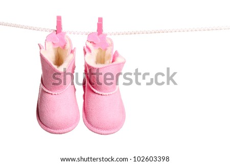 Pair of pink winter boots hanging on the clothesline. Image isolated on white background