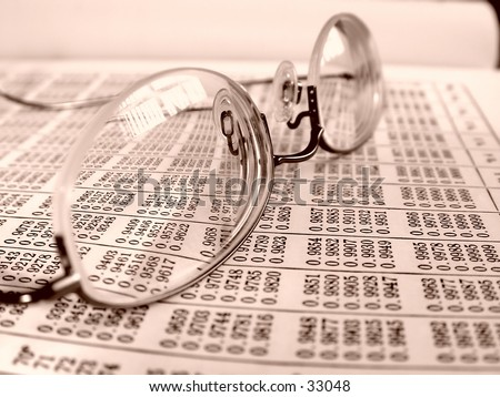 Pair of professional glasses on a business book with sepia tone