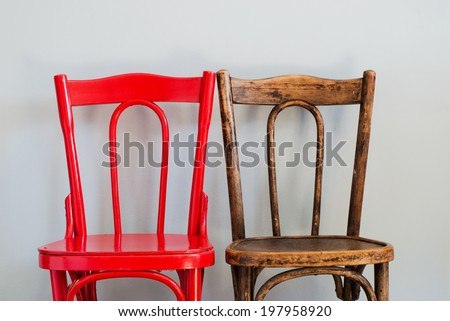 Pair of Red and Brown Chairs on a Grey Wall #197958920