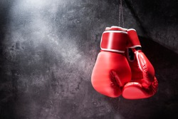 Pair of red boxing gloves hanging on the wall