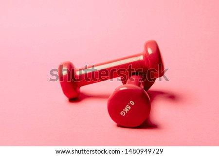 Pair of red 0.5 kg dumbbells on pink paper background.