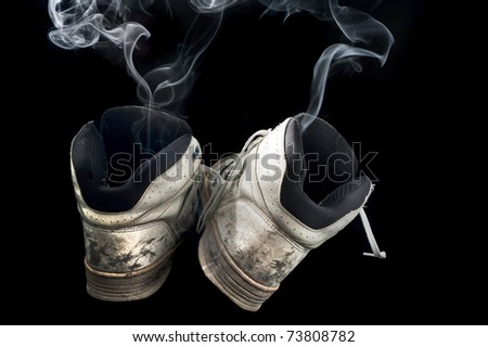 pair of rotten old sneakers on a black background