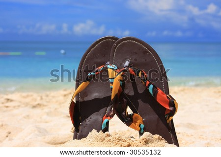 Pair of sandals in sand on island beach resort