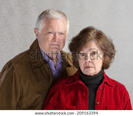 Pair of serious senior adults in jackets