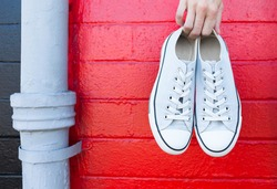 Pair of shoes against red brick background.