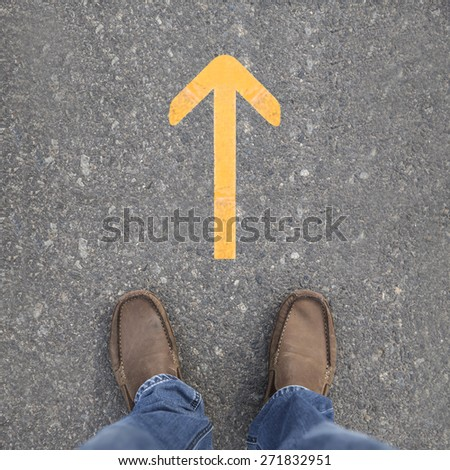 Pair of shoes on a road with yellow arrow #271832951