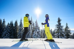 Pair of skiers standing on skis one against each other in helmet and goggles, watching on sun shine in center of blue sky. Winter family outdoors recreation concept. Snowy pine forest on background.