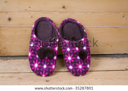 Pair of Slippers against a wooden door.