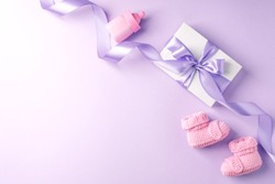 Pair of small baby socks and gift box on lilac background with copy space for your warm message, baby shower, first newborn party background, copy space
