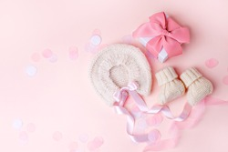 Pair of small baby socks, bonnet, gift box on pink background with copy space for your warm message, baby shower, first newborn party background, copy space, monochrome, banner