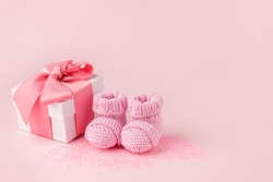 Pair of small pink baby socks and gift box on pink background with copy space for your warm message, baby shower, first newborn party background, copy space, monochrome