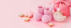 Pair of small pink baby socks, cookies, gift box on pink background with copy space for your warm message, baby shower, first newborn party background, copy space, monochrome, banner