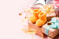 Pair of small yellow baby socks and gift box on pink background with gift present boxes and copy space for your warm message, baby shower, first newborn party background, banner