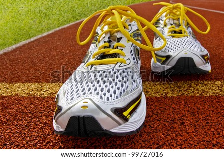 Pair of sports shoes standing on a tartan race track