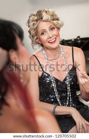 Pair of stylish mature women talking in hair salon