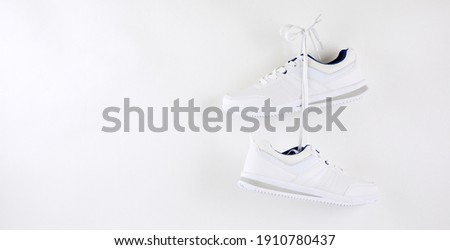 Pair of stylish sneakers hanging on wall. White shoe isolated on white background. Foto stock ©