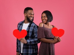 Pair of sweethearts with red hearts looking at each other with love, celebrating Valentine's Day on pink studio background. Beautiful black couple spending romantic times together