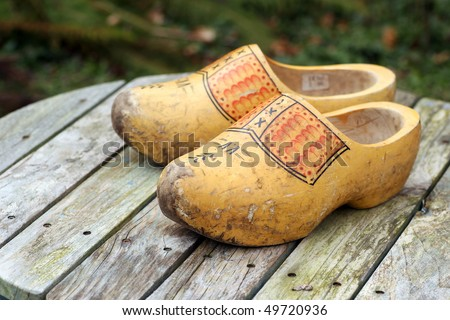 pair of traditional Dutch yellow wooden shoes on a wooden table